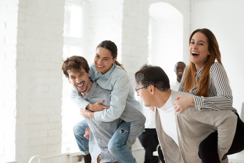 Cheerful young office people laughing and having funny piggyback. Cheerful young businesspeople laughing and having funny piggyback ride, happy employees royalty free stock image