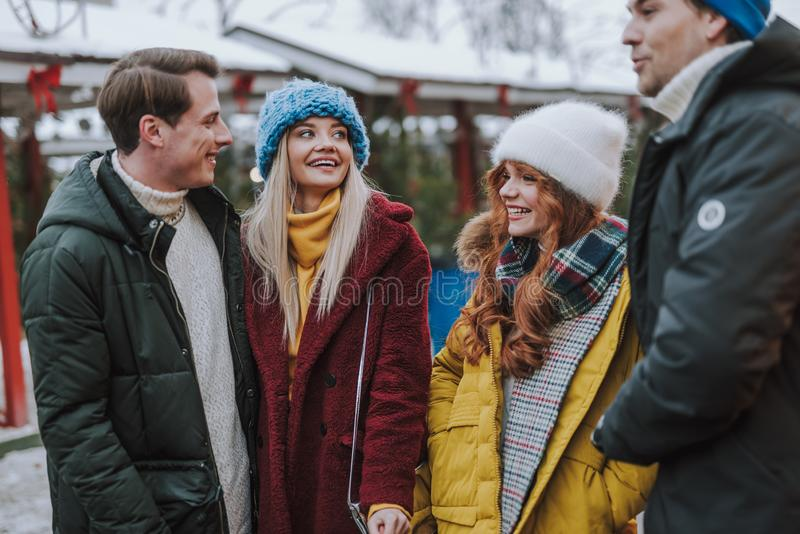 Cheerful young people discussing their plans for evening. Place of meeting. Happy girls wearing bright coats while walking on the Christmas market stock photos