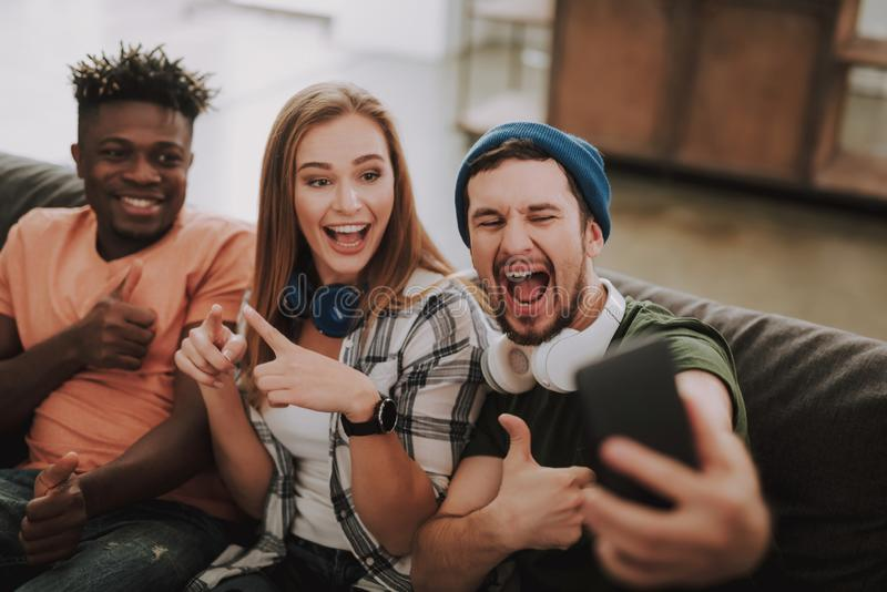 Cheerful young people making selfie while sitting on couch royalty free stock photos