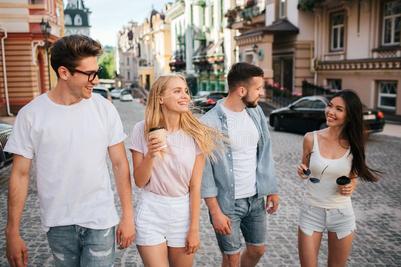 Cheerful young people are walking down the street. Three of them are looking at chinese girl. She holding glasses and stock image