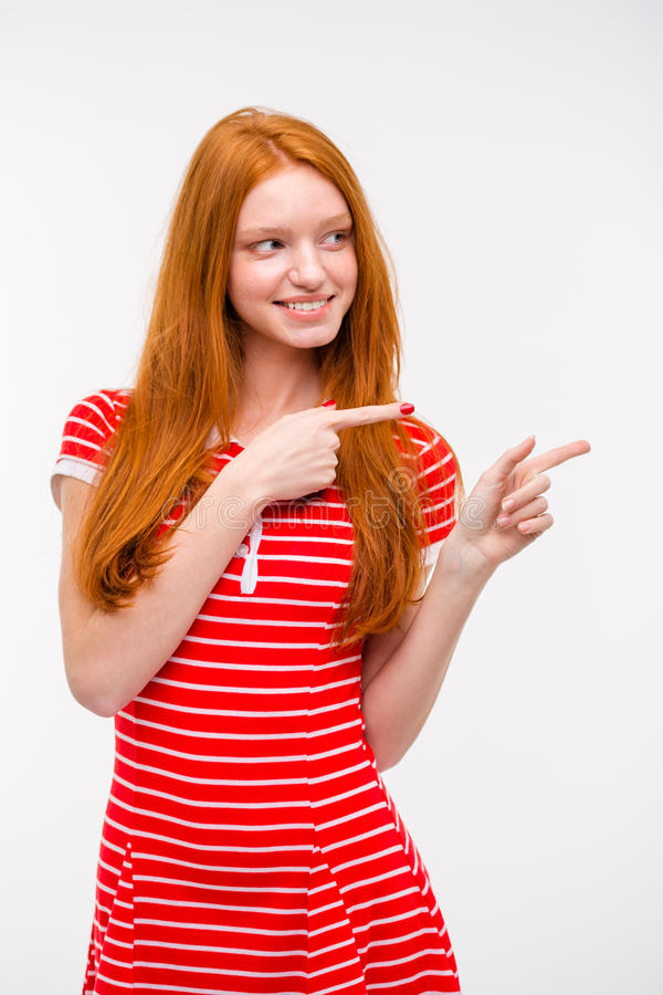 Cheerful young redhead woman pointing away stock photos