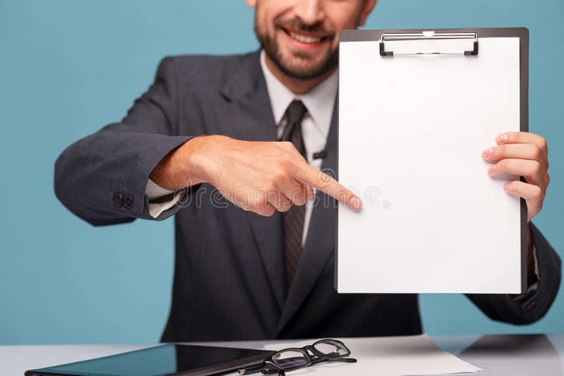 Cheerful young reporter is presenting documents at stock photography