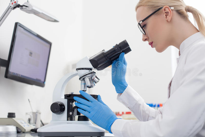Cheerful young researcher is making the experiments stock photography