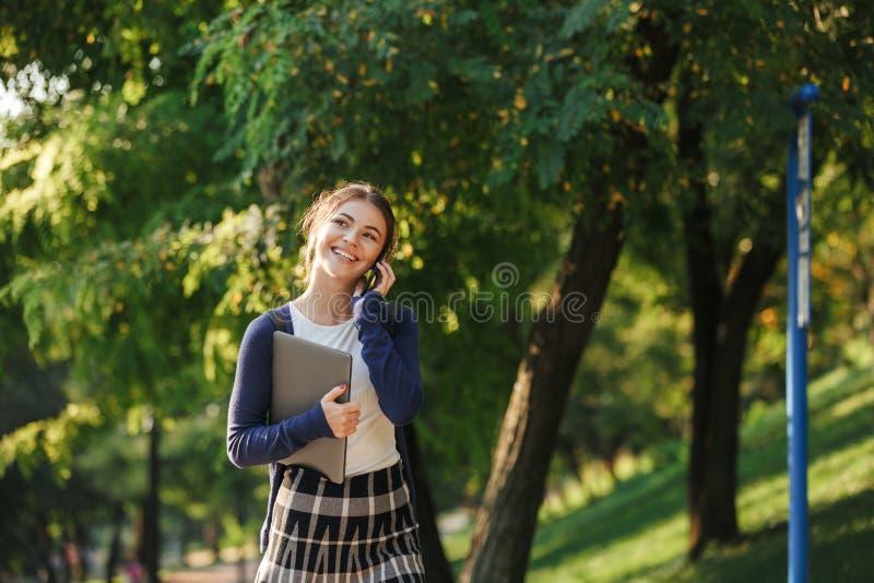 Cheerful young school girl walking outdoors stock image