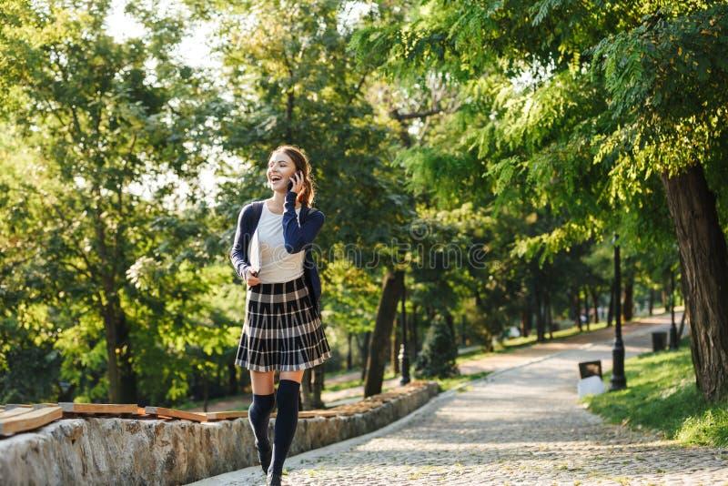 Cheerful young school girl walking outdoors stock photography