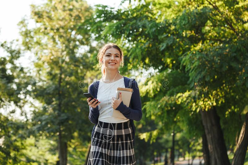 Cheerful young school girl walking outdoors royalty free stock photos