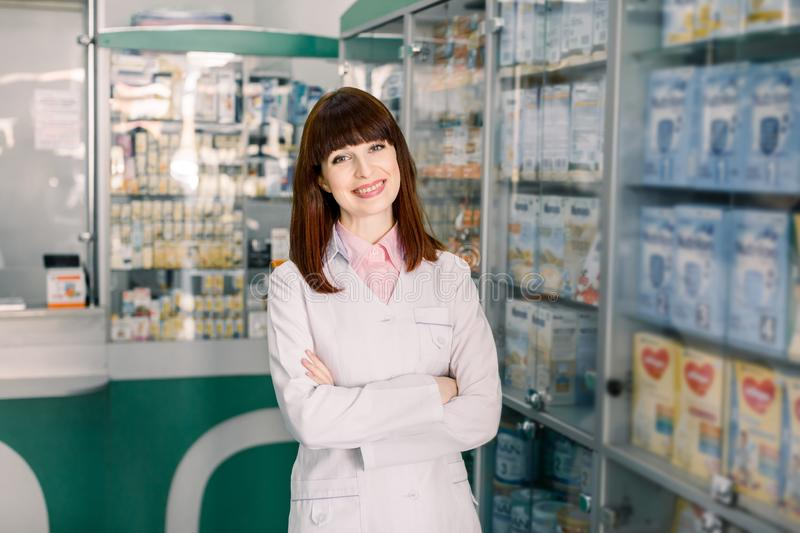 Cheerful young smiling Caucasian pharmacist chemist woman standing in pharmacy drugstore stock photography