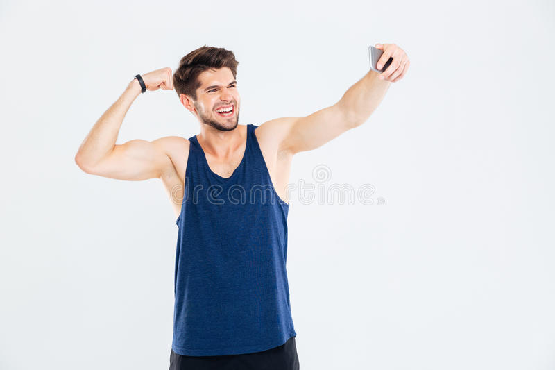Cheerful young sportsman showing biceps and taking selfie with smartphone royalty free stock photography