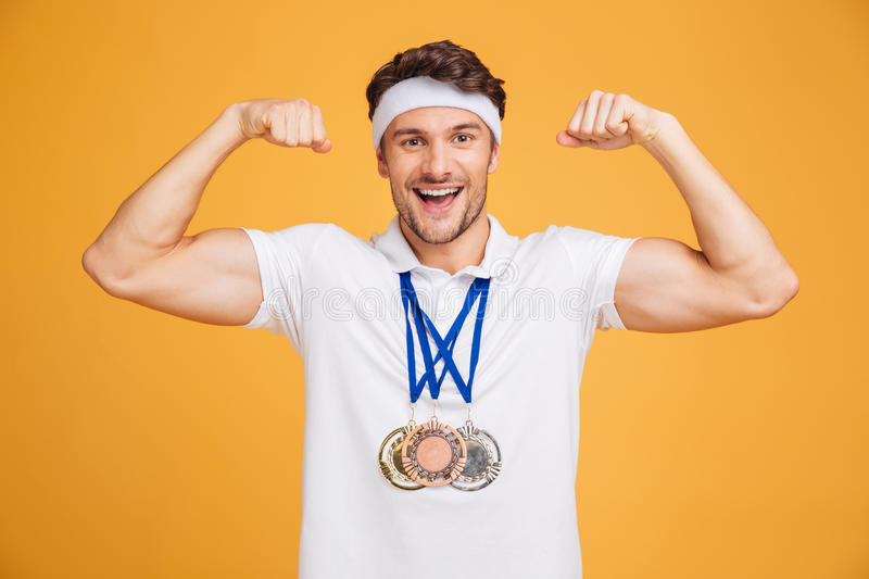 Cheerful young spotrsman with three medals showing biceps royalty free stock images