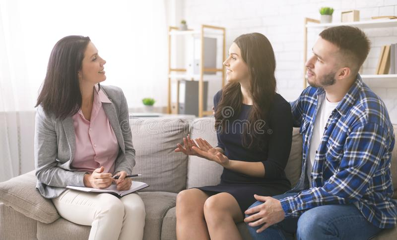 Cheerful young spouses talking to professional marital counselor. Successful couple therapy. Cheerful young spouses talking to professional marital counselor at stock images