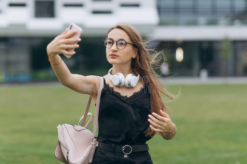 Portrait of a happy cheerful smiling young student schoolgirl lady with long hair wearing eyeglasses looking camera take royalty free stock images