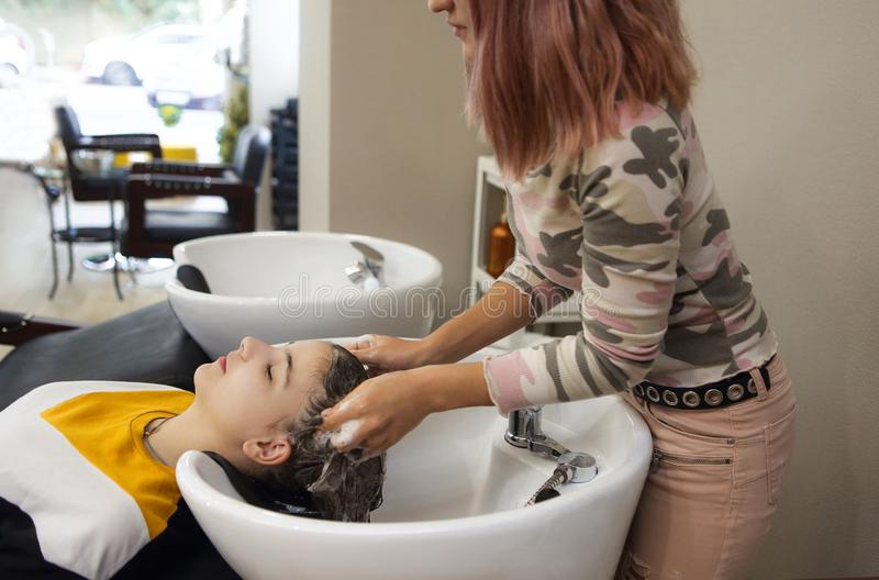 Cheerful young teen girl enjoying head massage while getting her hair washed by a professional hairdresser stock photos