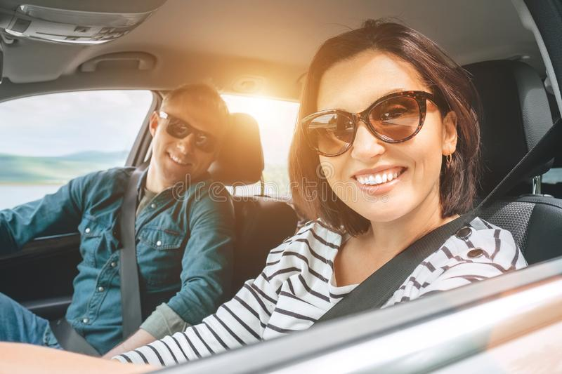 Cheerful young traditional couple has a long auto journey. Safety riding car concept wide angle inside car view image royalty free stock photo