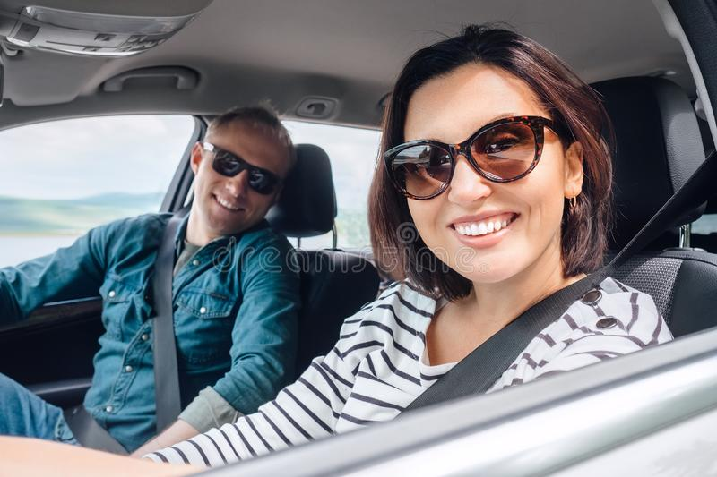 Cheerful young traditional couple has a long auto journey. Safety riding car concept wide angle inside car view image royalty free stock images