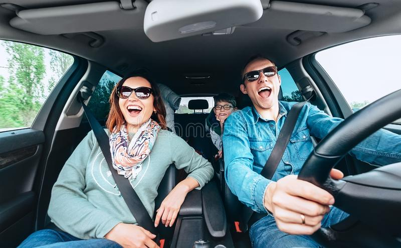 Cheerful young traditional family has a long auto journey and singing aloud the favorite song together. Safety riding car concept. Wide angle inside car view royalty free stock photos