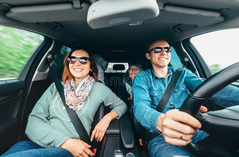 Cheerful young traditional family has a long auto journey and singing aloud the favorite song together. Safety riding car concept. Wide angle inside car view stock image