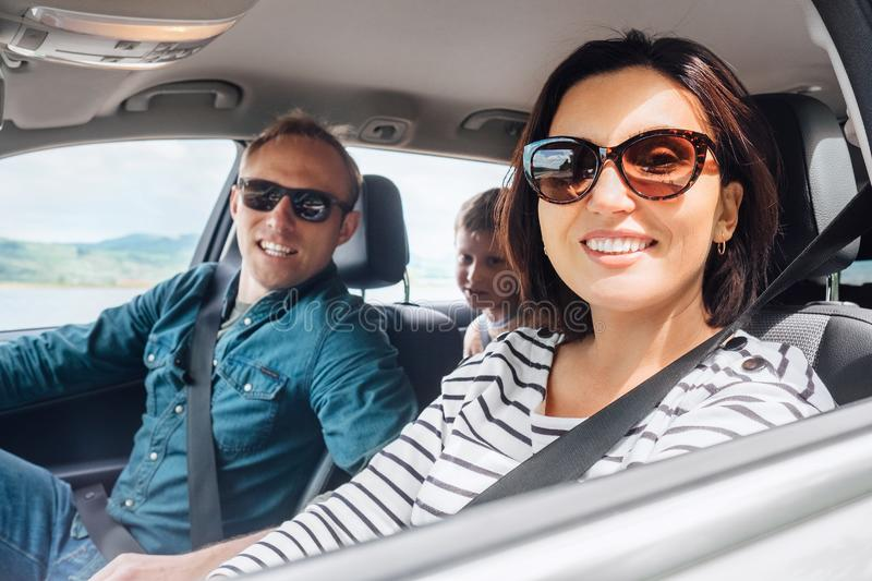 Cheerful young traditional family has a long auto journey and smiling together. Safety riding car concept inside car wide angle. View royalty free stock photo