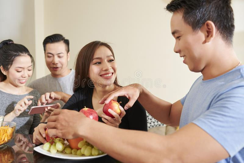 Young people eating fruits at party stock photos