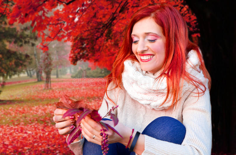 cheerful young woman with autumn leafs in front of f stock photography