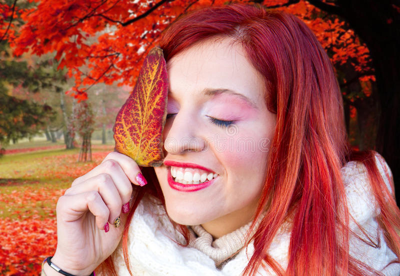 Cheerful young woman with autumn leafs in front of f stock image