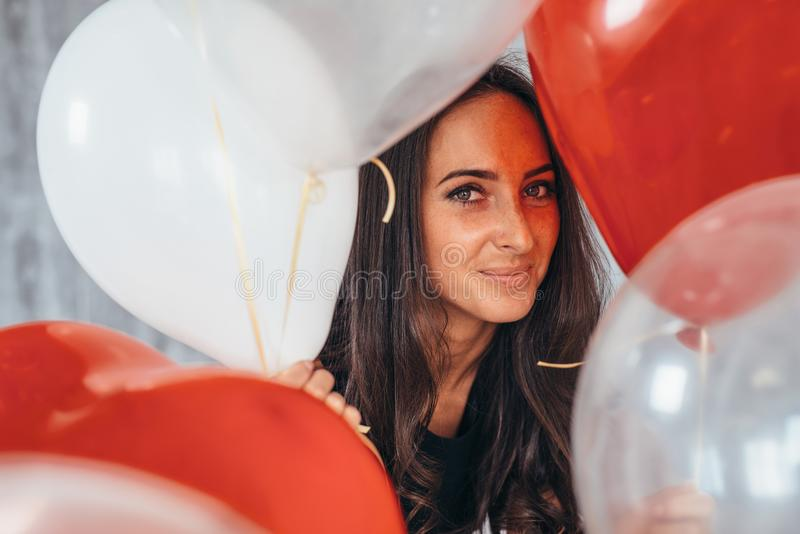 Cheerful young woman with balloons standing and smiling stock photo