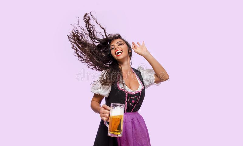 Cheerful young woman in Bavarian dress holding beer stock photo
