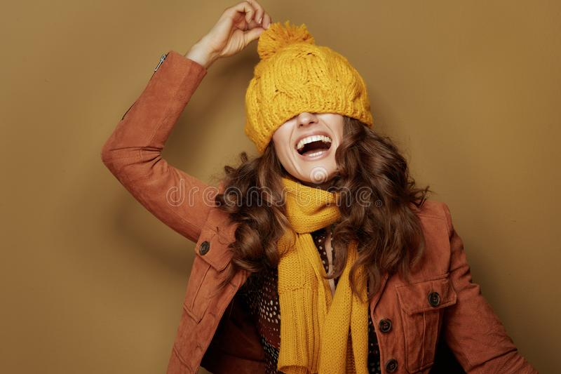 Cheerful young woman with beret over eyes on beige background royalty free stock images