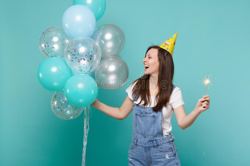 Cheerful young woman in birthday hat looking aside hold burning sparkler, celebrating with colorful air balloons. Isolated on blue turquoise background royalty free stock photo