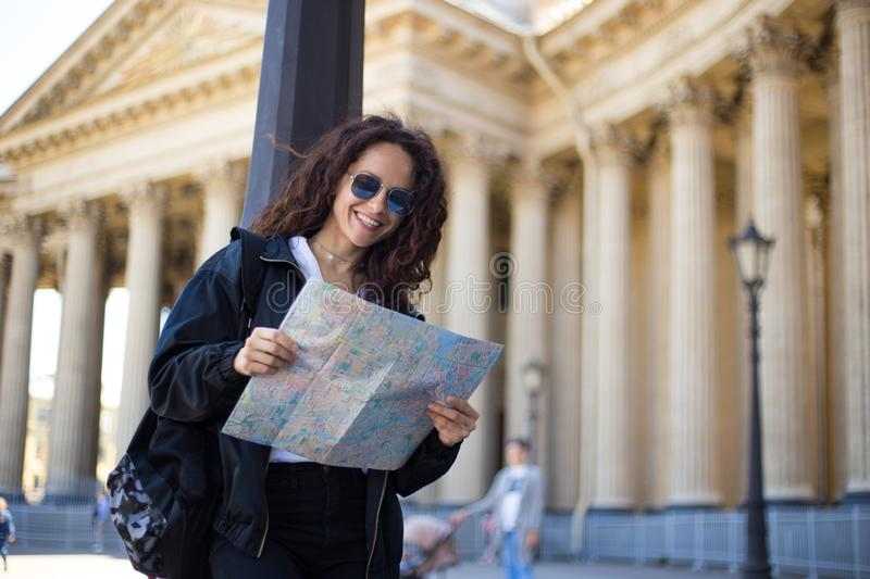 Cheerful young woman in black, in sunglasses with a city paper map in hands, have a backpack, on cathedral background. royalty free stock photography