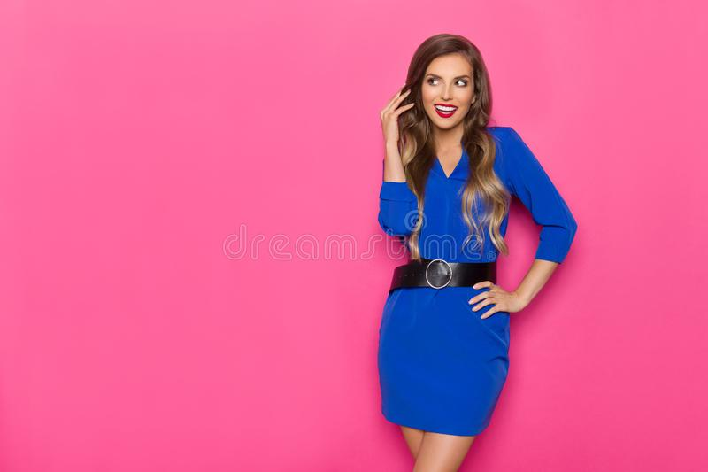 Cheerful Young Woman In Blue Mini Dress With Black Belt Is Looking Away And Talking. Beautiful young woman in blue mini dress and black belt is posing with hand stock photography