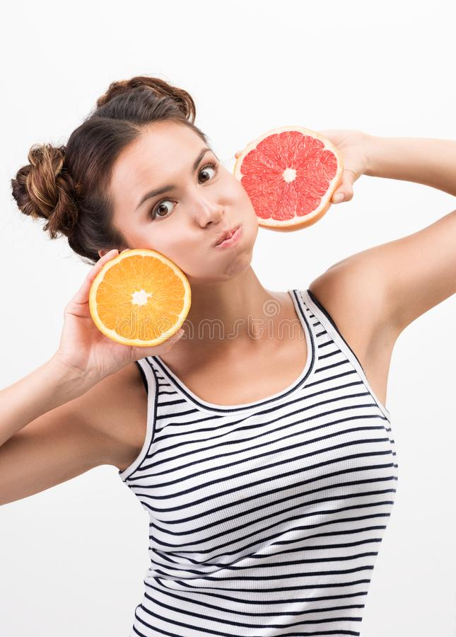 Cheerful young woman with citrus fruit, put to the face. Cheerfulness and good mood. Striped tank top and hairstyle. Neutral white background royalty free stock photos
