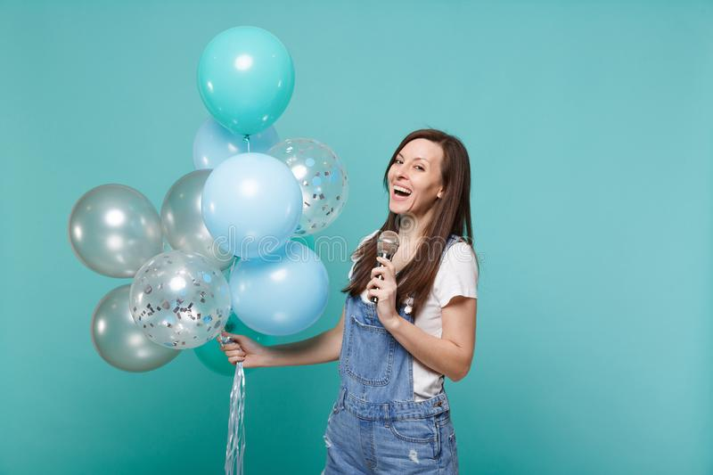 Cheerful young woman in denim clothes sing song in microphone, celebrating and holding colorful air balloons isolated on. Blue turquoise background. Birthday stock photo