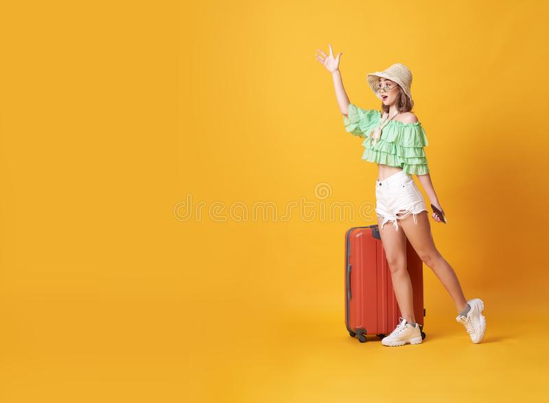 Cheerful young woman dressed in summer clothes standing with a suitcase and say hello at copy space isolated over yellow. Background royalty free stock photo