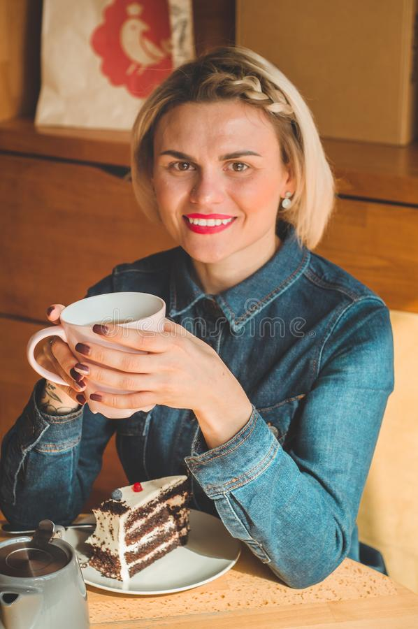 Cheerful young woman drinking warm coffee or tea enjoying it while sitting in cafe stock photo