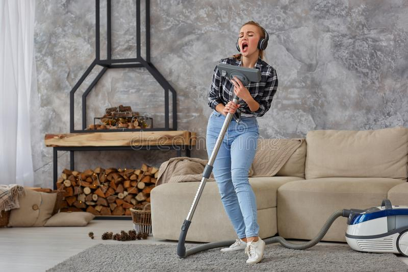 Cheerful young woman enjoying solo singing with vacuum cleaner while cleaning house royalty free stock photo