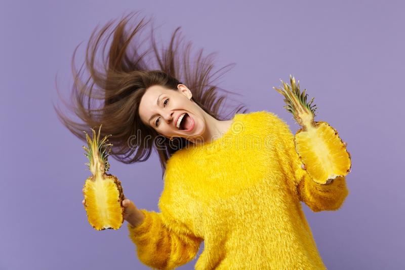 Cheerful young woman in fur sweater with flowing hair hold halfs of fresh ripe pineapple fruit isolated on violet pastel royalty free stock image