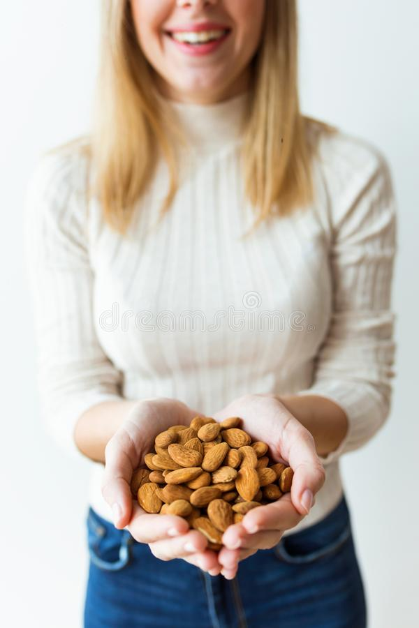 Cheerful young woman hands holding almonds nuts on white background. Shot of cheerful young woman hands holding almonds nuts on white background royalty free stock photo