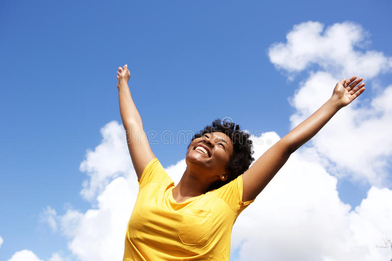 Cheerful young woman with hands raised towards sky. Portrait of cheerful young woman standing outside with her hands raised towards sky stock photography