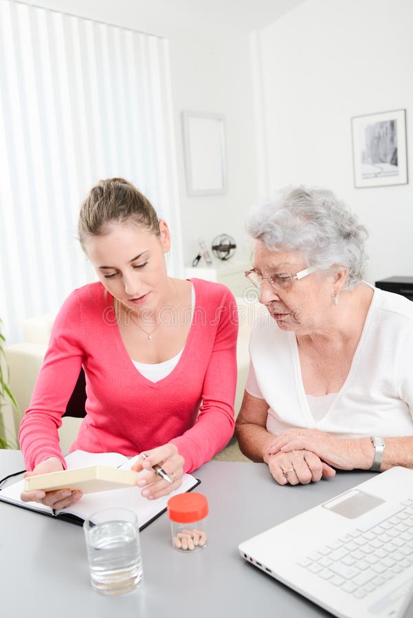 Cheerful young woman helping an elderly woman with pills medical prescription. Cheerful young women helping an elderly women with a pills medical prescription royalty free stock image