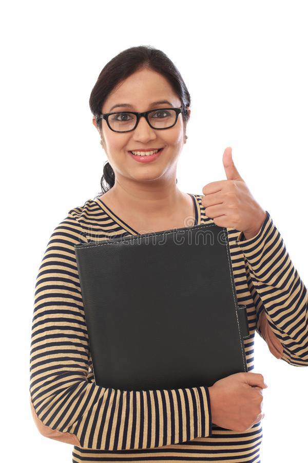 Cheerful young woman holding a folder. Against white royalty free stock photography