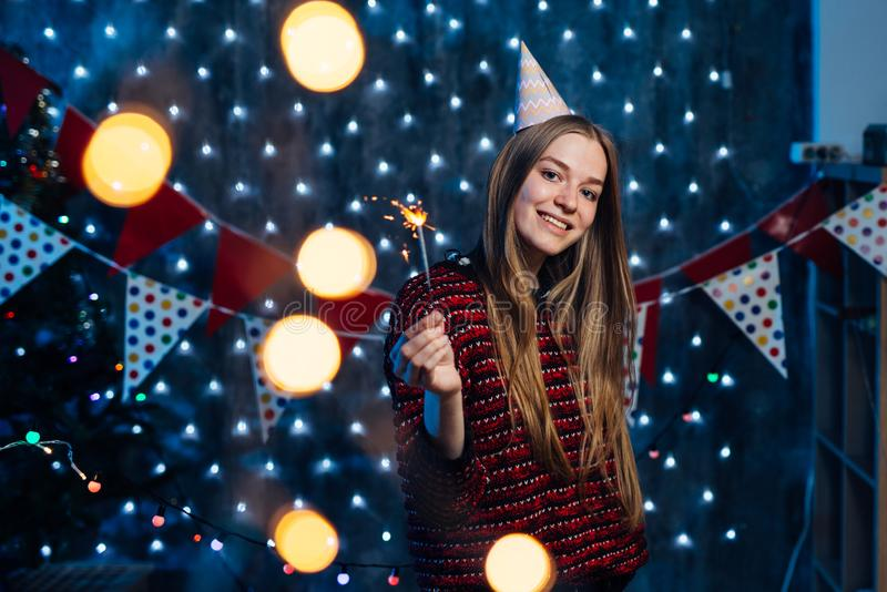 Cheerful young woman holding sparkler in hand. Christmas New Year royalty free stock photo