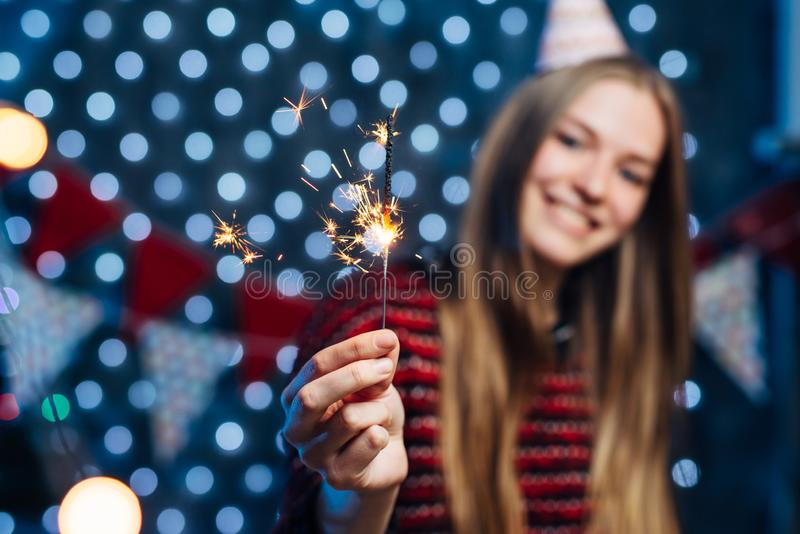 Cheerful young woman holding sparkler in hand. Christmas New Year royalty free stock photos
