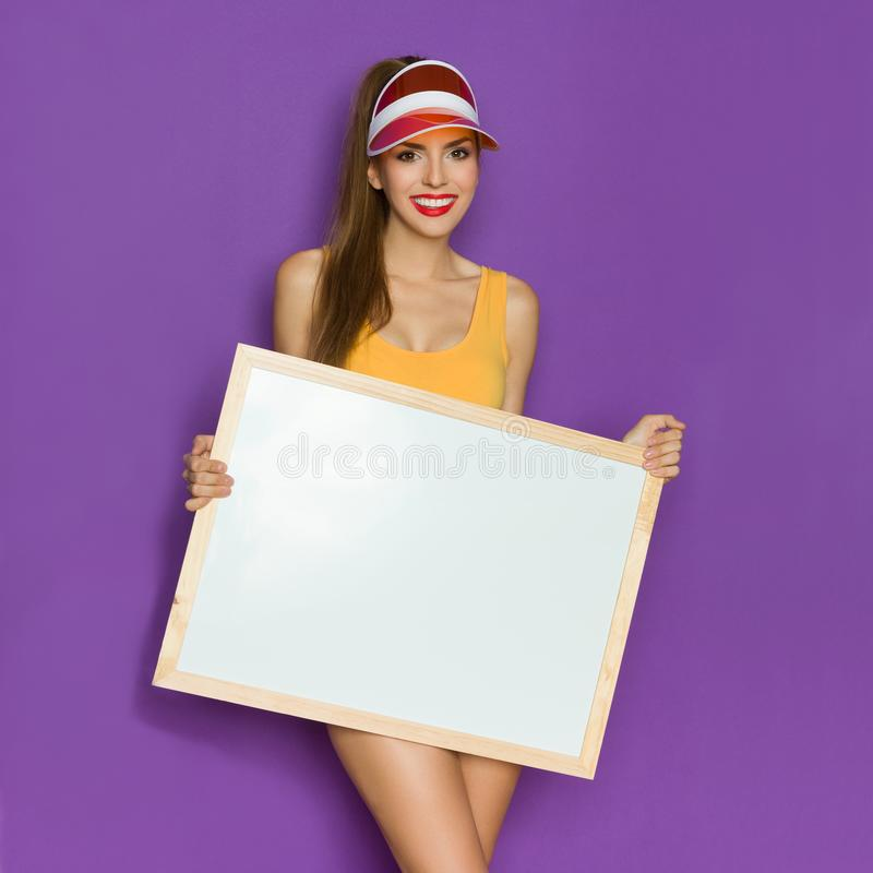Cheerful Young Woman Holding White Image In Wooden Frame royalty free stock image