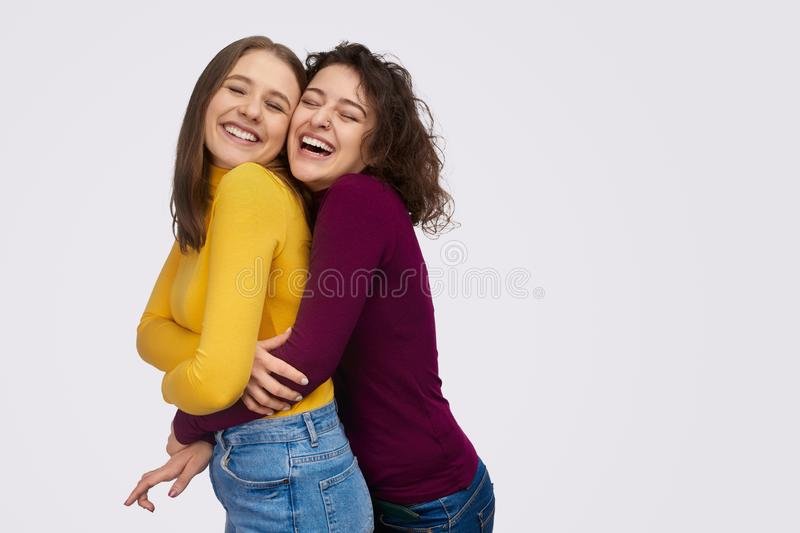 Cheerful young woman hugging best friend stock image