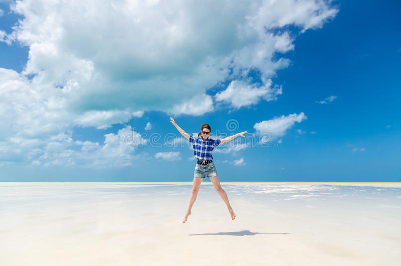 Cheerful young woman in joy jumping with arms out over desert sea lagoon stock image