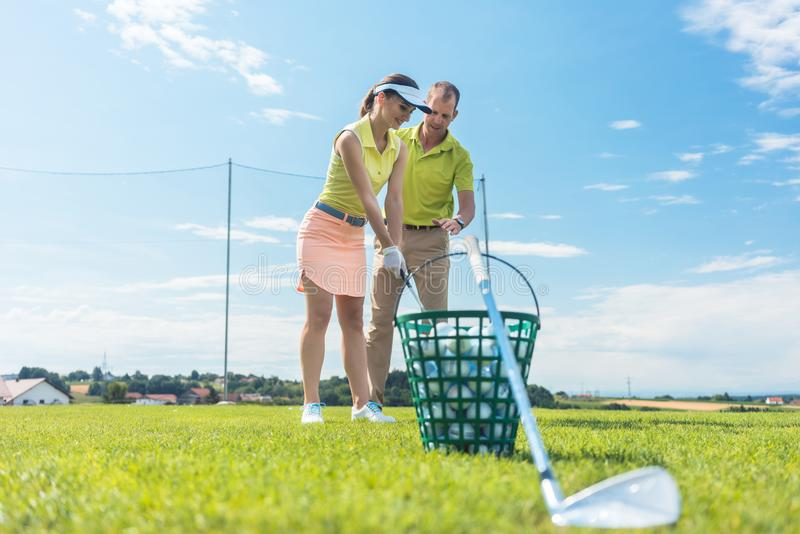 Cheerful young woman learning the correct grip and move for using the golf club. Full length of a cheerful young women learning the correct grip and move for stock image