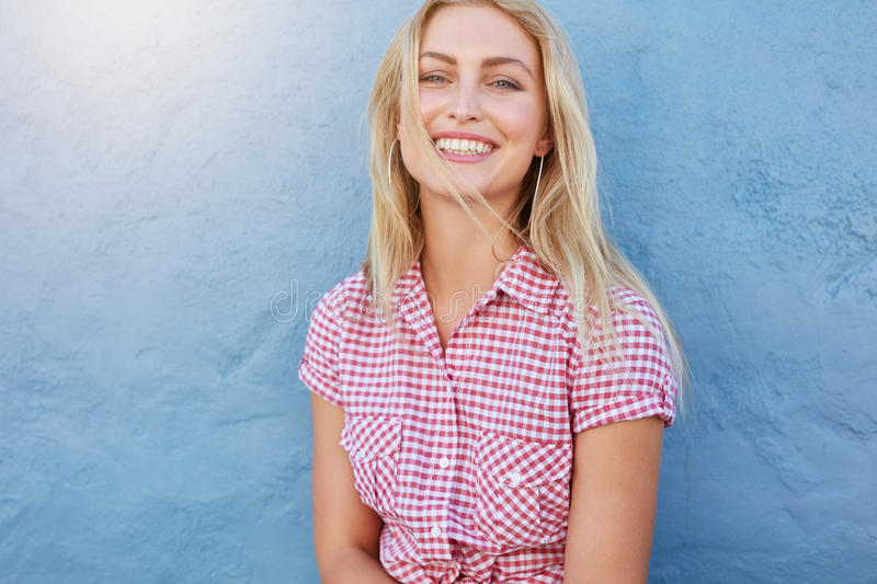 Cheerful young woman looking at camera and smiling royalty free stock images