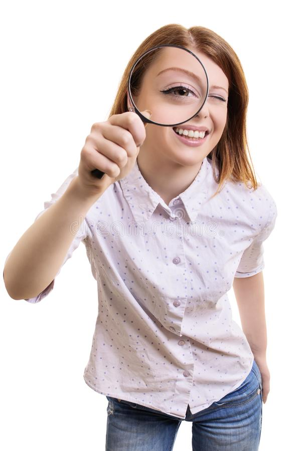 Cheerful young woman looking through magnifying glass. Close up portrait of a cheerful pretty young woman looking at camera through magnifying glass, isolated on stock images