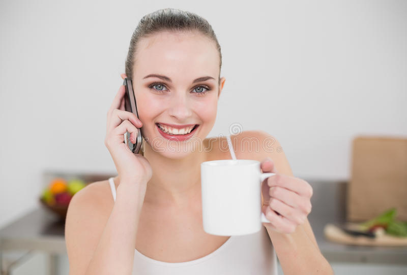 Cheerful young woman making a phone call and holding a mug looking at camera stock images