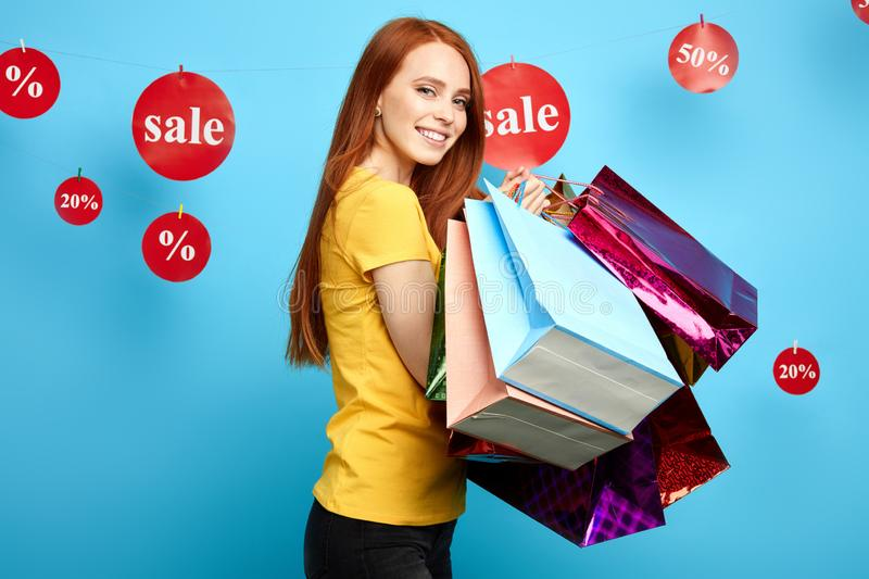 Cheerful young woman with many packets posing too the camera royalty free stock photography